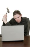Man hammers computer. Frustrated guy hammering his laptop computer Royalty Free Stock Photos