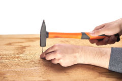 Man hammers a nail with a hammer Royalty Free Stock Images