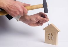 Man hammers a nail with a hammer in a miniature wooden house on royalty free stock photo