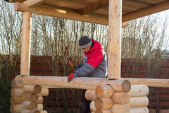 Man hammers wooden rail in the beam Royalty Free Stock Photo