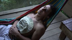 Man in hammock laying alone abandoned and getting mad distracted, loneliness mentally ill