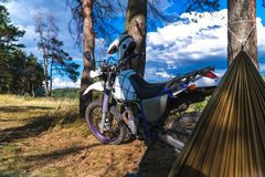 Man in a hammock on pine forest mountain, outdoor traveler relax, enduro off road motorcycle royalty free stock photos