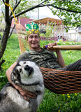 Man in a hammock with  pipe. A man in a hammock with a pipe and a huge dog Royalty Free Stock Images