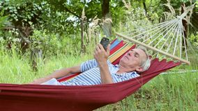 Man in a hammock playing on the phone stock footage