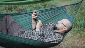 A man in a hammock touch phone. Man in the woods with a beard and glasses. A man in a hammock touch smartphone. Man in the woods with a beard and glasses stock video footage
