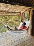 Man in hammock at tropical villa. Man relaxing in hammock at tropical villa royalty free stock photos