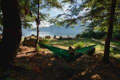 Man in hammock under trees on beach near lake Stock Photo