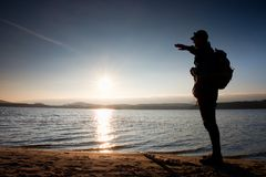 Man with hand in the air. Tall hiker in dark sportswear with sporty backpack stands on beach enjoy sunset at horizon Royalty Free Stock Image