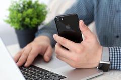 Man hand Apple Watch holding iPhone 7 Jet Black Onyx Stock Photography