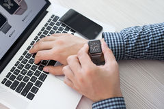 Man hand with Apple Watch and Macbook on the desk Royalty Free Stock Photo