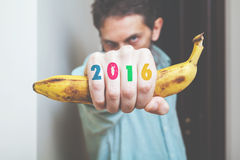 Man hand with banana and numbers on fingers. Man holds banana in his hand in front of him. Monkey symbol. On fingers painted figures 2016 royalty free stock photo