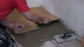 Man hand bond ceramic floor tile at home. Home renovation. stock footage