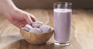 Man hand bring violet macarons with blueberry yogurt in glass on wood table Royalty Free Stock Image