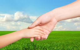 Man hand and a child hand holding each other on the background Royalty Free Stock Photography