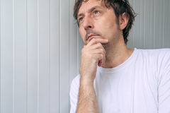Man with hand on chin thinking deep thoughts Royalty Free Stock Image