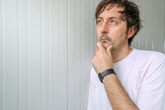 Man with hand on chin thinking deep thoughts Stock Image