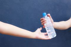 Man hand clean plastic bottle full of fresh drinking water to woman on background.  stock image