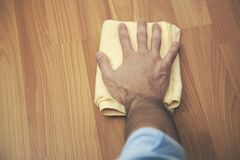 Man hand cleaning an hardwood floor with a microfiber cloth.  royalty free stock photo