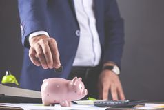 Man hand coin with piggy bank and calculator stock image