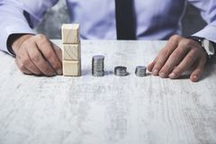 Man hand coins with cubes. Man hand coins with wooden cubes on desk stock photography