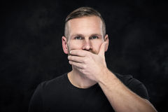 Man with hand covering his mouth Royalty Free Stock Images