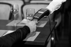 Man hand with credit card swipe through terminal for sale. In restaurant. Credit card payment and electronic bank concept stock photo