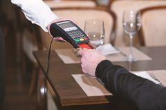 Man hand with credit card swipe through terminal for sale. In restaurant. Credit card payment and electronic bank concept stock photography