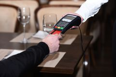 Man hand with credit card swipe through terminal for sale. In restaurant. Credit card payment and electronic bank concept royalty free stock photography