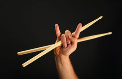 Man hand with crossed drumsticks and devil horns over black Royalty Free Stock Image