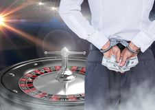 Man in hand cuffs with money and roulette machine Royalty Free Stock Photos