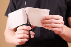 Man hand cut white paper with scissors. Stock Photography