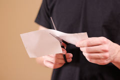Man hand cut white paper with scissors. Royalty Free Stock Photo