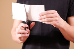 Man hand cut white paper with scissors. Stock Images