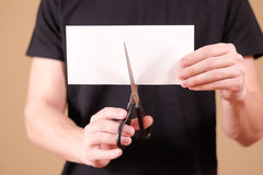 Man hand cut white paper with scissors. Royalty Free Stock Photos