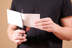 Man hand cut white paper with scissors. Stock Image
