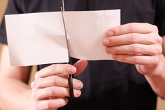 Man hand cut white paper with scissors. Stock Photos