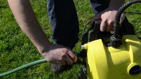 Man hand detach water hose to high pressure wash equipment stock video footage