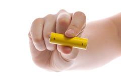 man hand die een gele batterij of batterij op een witte geïsoleerde achtergrond houden Stock Fotografie