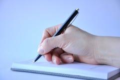 Man hand die een pen houden en in een notitieboekje schrijven royalty-vrije stock afbeelding