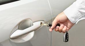 Man hand die een sleutel opnemen in het deurslot van een auto Stock Fotografie