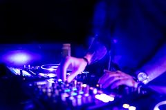 Man hand disc jockey mixing and blending music tracks. Soft view of man hand disc jockey mixing and blending music tracks on his deck in the darkness of a party royalty free stock image