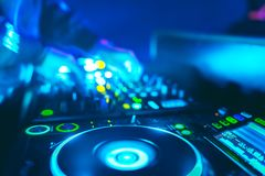 Man hand disc jockey mixing and blending music tracks. Soft view of man hand disc jockey mixing and blending music tracks on his deck in the darkness of a party stock image