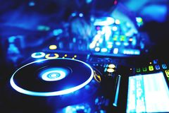 Man hand disc jockey mixing and blending music tracks. Soft view of man hand disc jockey mixing and blending music tracks on his deck in the darkness of a party royalty free stock photos