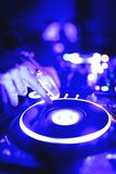 Man hand disc jockey mixing and blending music tracks. Soft view of man hand disc jockey mixing and blending music tracks on his deck in the darkness of a party royalty free stock images