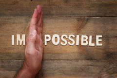 Man hand dividing the letters IM from the word impossible so it Stock Photos