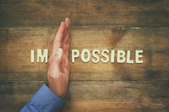 Man hand dividing the letters IM from the word impossible so it Stock Photo