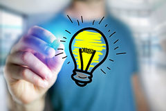 Man hand drawing bulb lamp icon on a futuristic interface - tech. View of Man hand drawing bulb lamp icon on a futuristic interface - technology concept Royalty Free Stock Photography