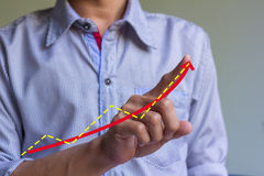 Man hand drawing a graph. Stock Image