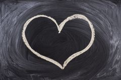 Man hand drawing a heart with chalk in a chalkboard. Male hand drawing a heart with chalk in a chalkboard stock photo