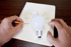 Man hand drawing a light bulb on note paper (idea concept) Stock Photos